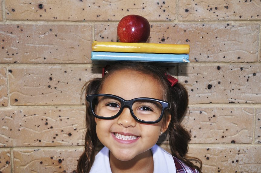 "alt=""Girl smiling with books and apple on her head."""